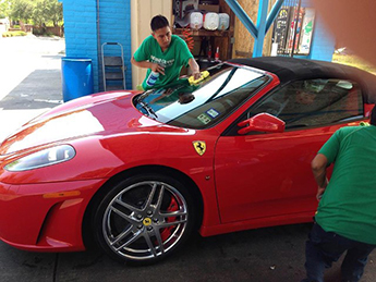 Workers Cleaning Red Sports Car